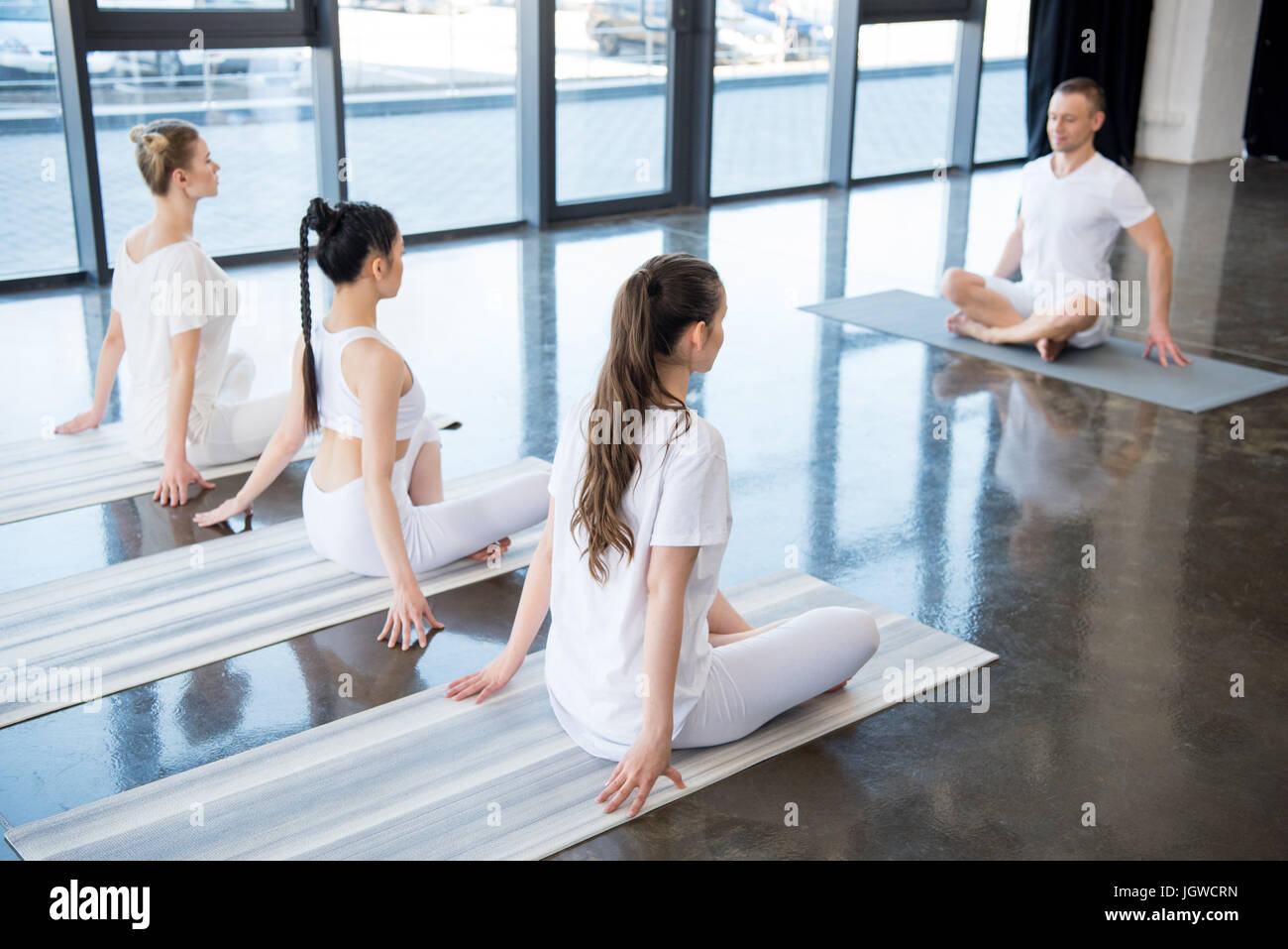 young women sitting in lotus pose with instructor indoors - Stock Image