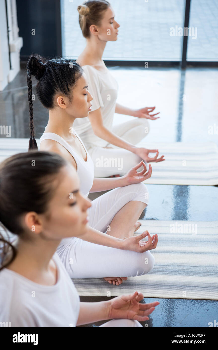 multiethnic women with eyes closed meditating in lotus pose with gyan mudra indoors - Stock Image