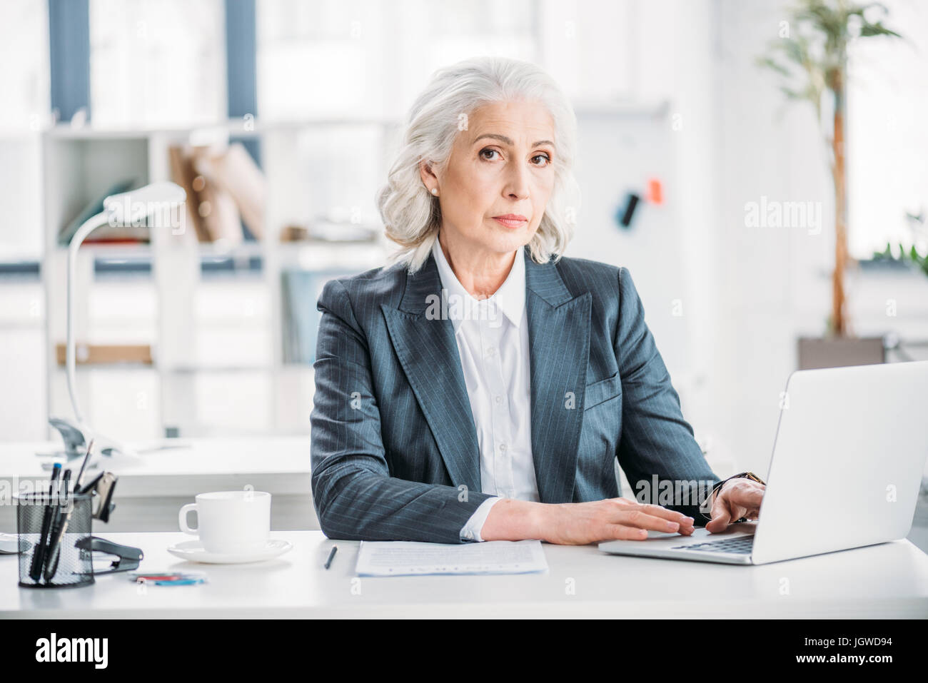 portrait of confident businesswoman typing on laptop at workplace in modern office - Stock Image