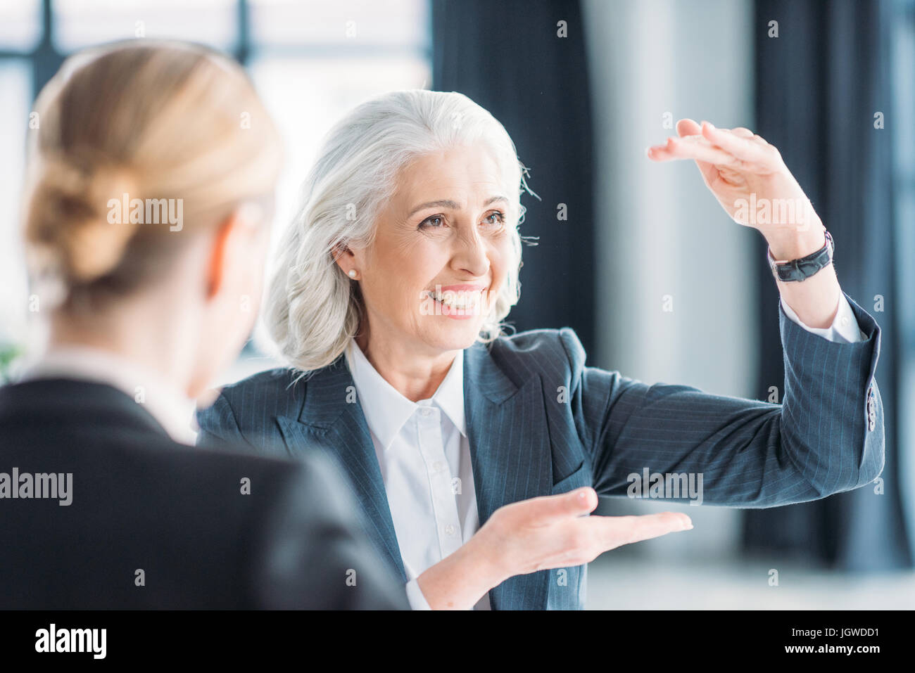 senior businesswoman showing something to colleague on meeting in office - Stock Image