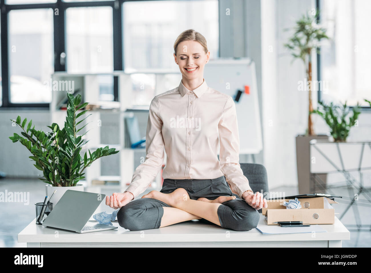 happy businesswoman meditating in lotus position on messy table in office - Stock Image