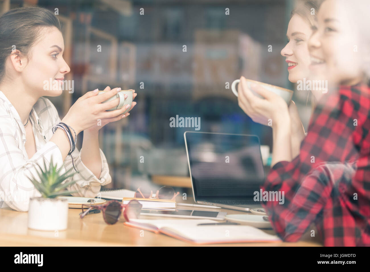 friends spend time together on coffee break in cafe - Stock Image
