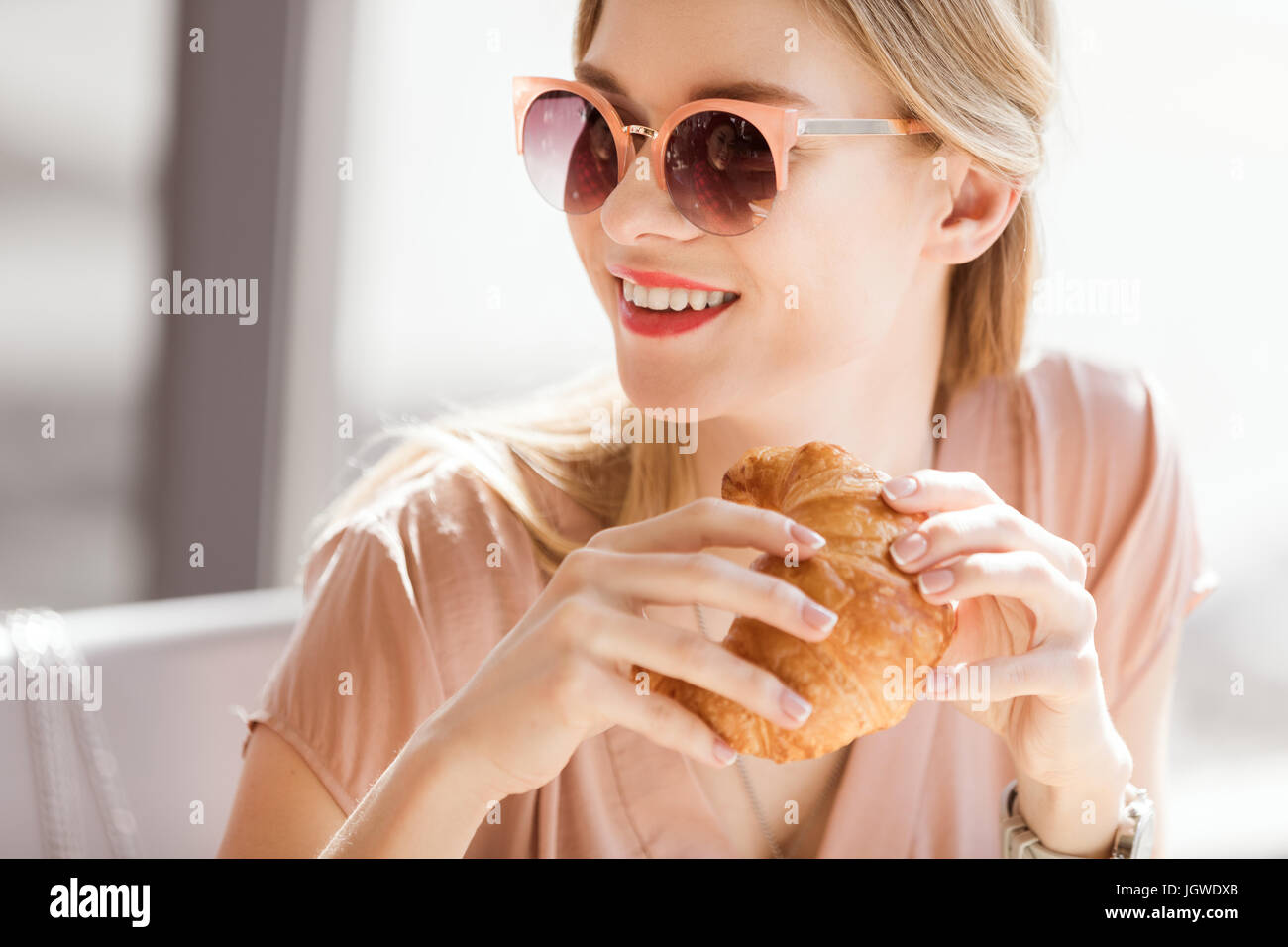 young woman eating croissant while sitting in cafe, coffee break Stock Photo