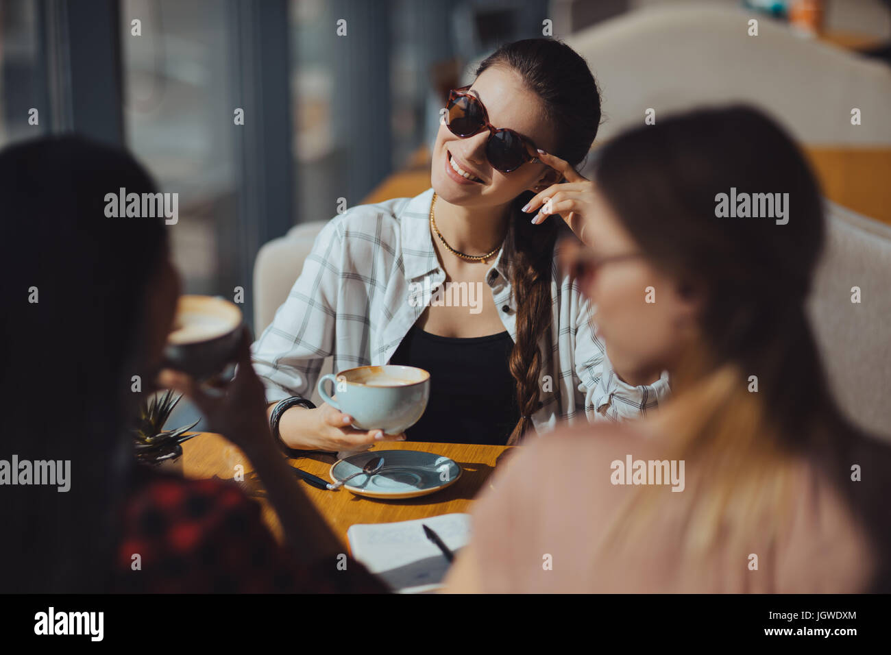 young attractive multicultural women on coffee break in cafe - Stock Image