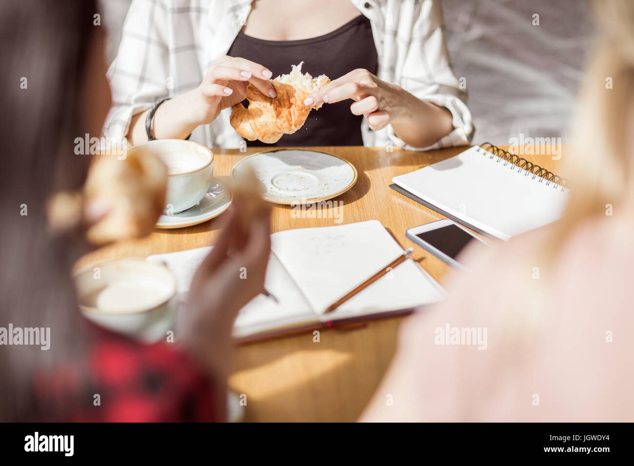 young girls eating croissants and drinking coffee at cafe, coffee break - Stock Image