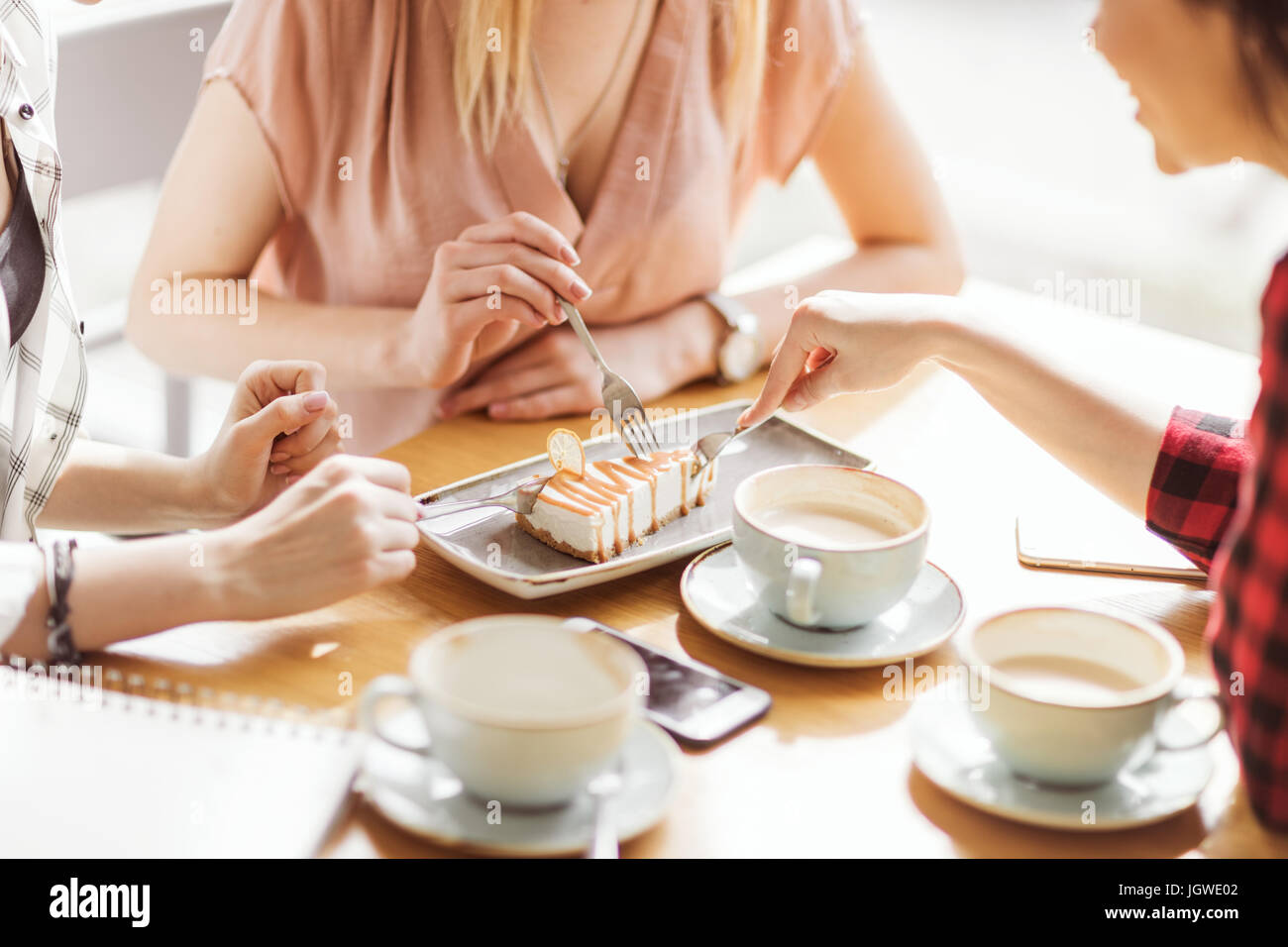 young girls eating cake and drinking coffee at cafe, coffee break - Stock Image