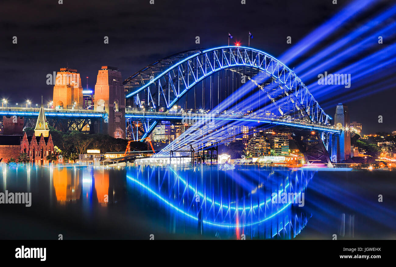 Sydney harbour bridge illuminated during vivid sydney light festival. Bright blue light beams project from Overseas - Stock Image