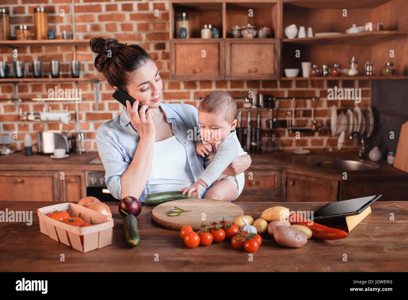 Portrait of mother with son talking on smartphone and preparing dinner in the kitchen - Stock Image