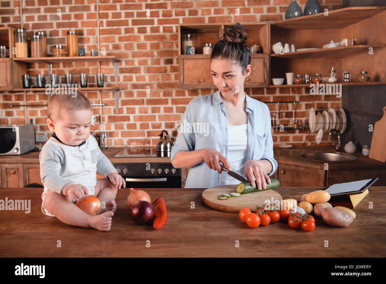 Happy young family cooking breakfast together. Mother chopping cucumber on cutting board while her son sitting near - Stock Image