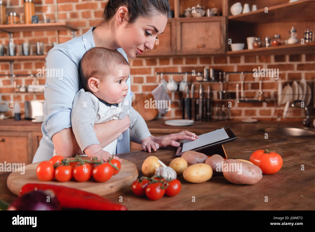 Mother with her baby son looking for recipe on digital tablet before cooking dinner in the kitchen - Stock Image