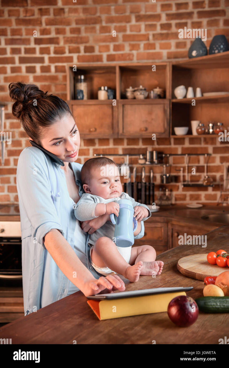 Young mother holding her son on arms and talking on smartphone during dinner preparation in the kitchen - Stock Image