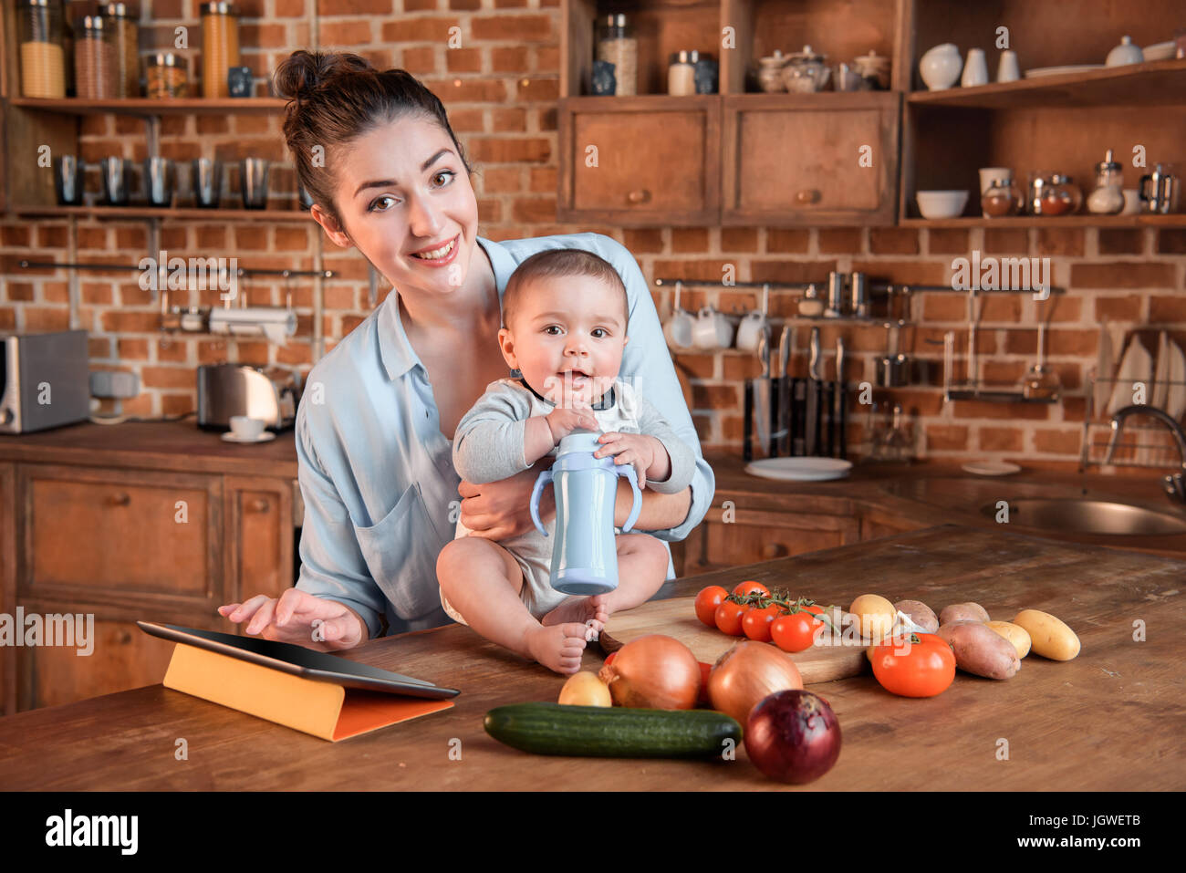 Portrait of young mother with her little son cooking dinner together and using digital tablet in the kitchen - Stock Image