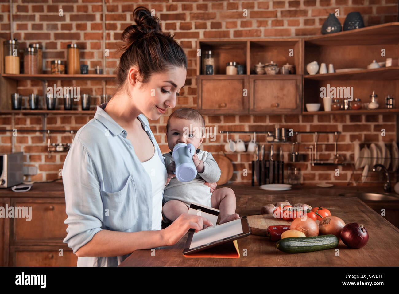 Portrait of mother and baby boy shopping online with digital tablet and credit card - Stock Image
