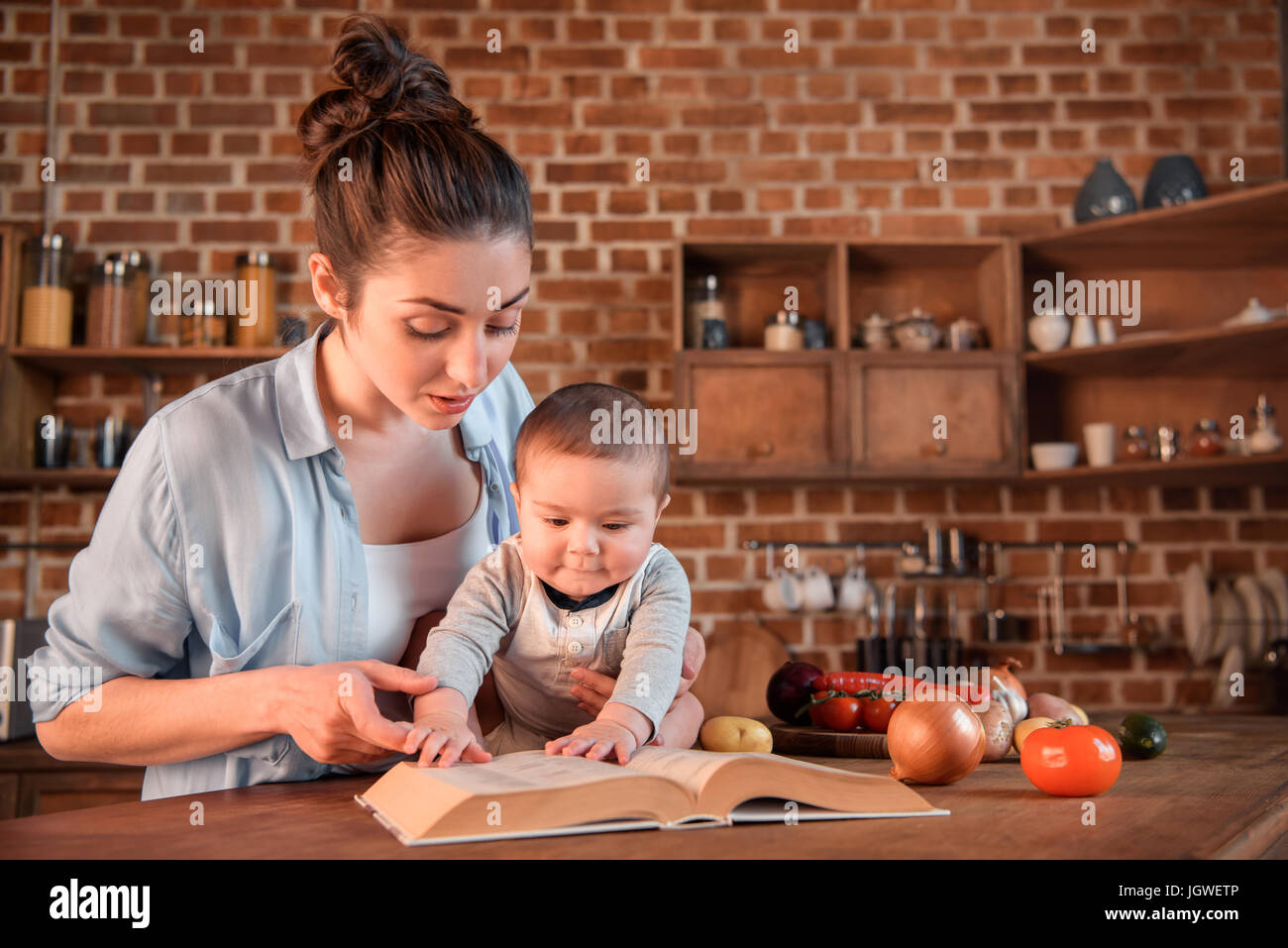 Mother with her baby son reading recipe book before preparing dinner in the kitchen - Stock Image