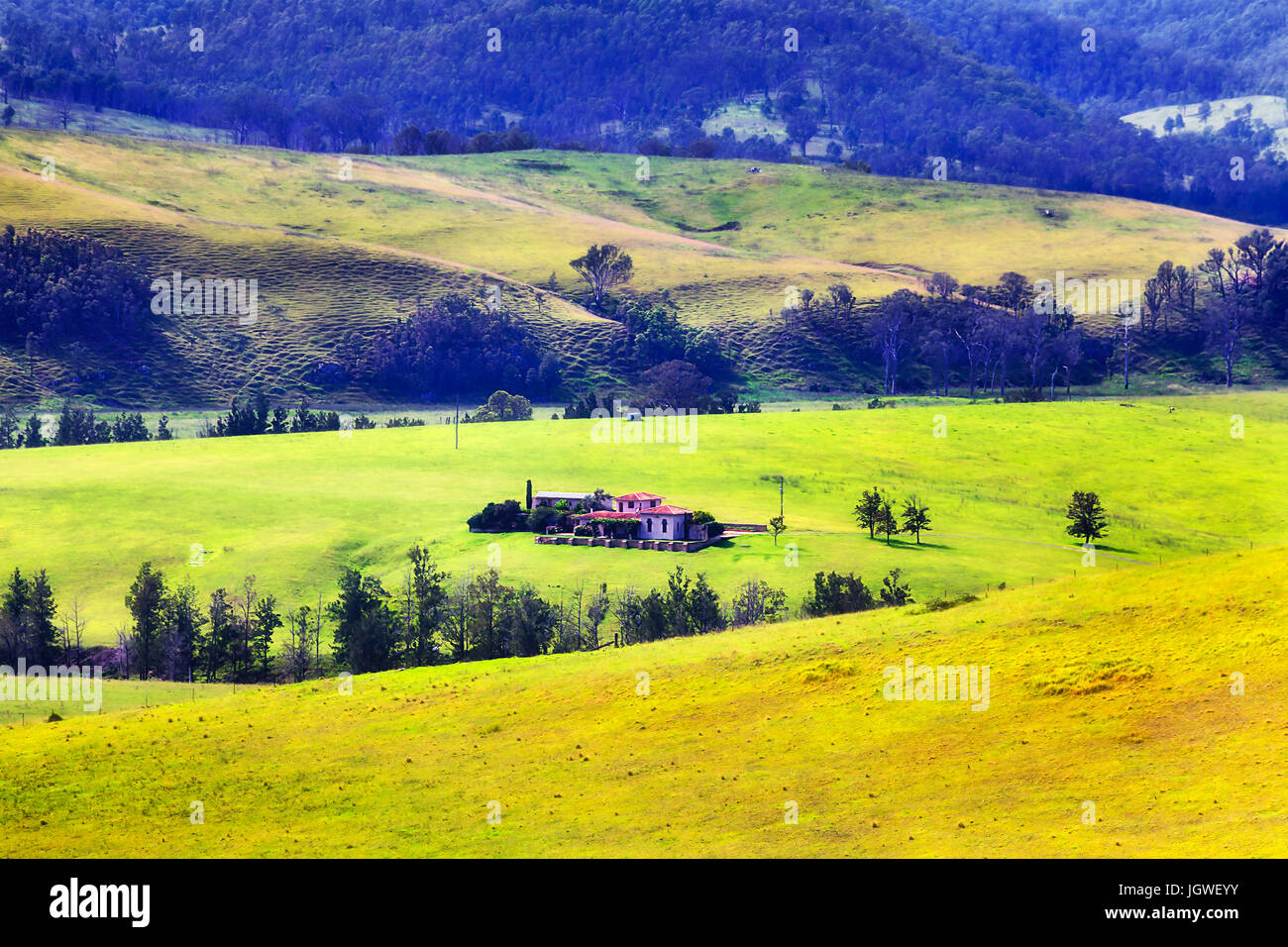 Remote agricultural developed farm to grow cattle in a middle of green grass pasture surrounded by hill ranges and - Stock Image
