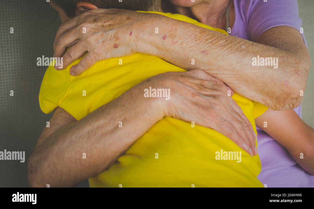 An elderly woman hugging a young boy - Stock Image