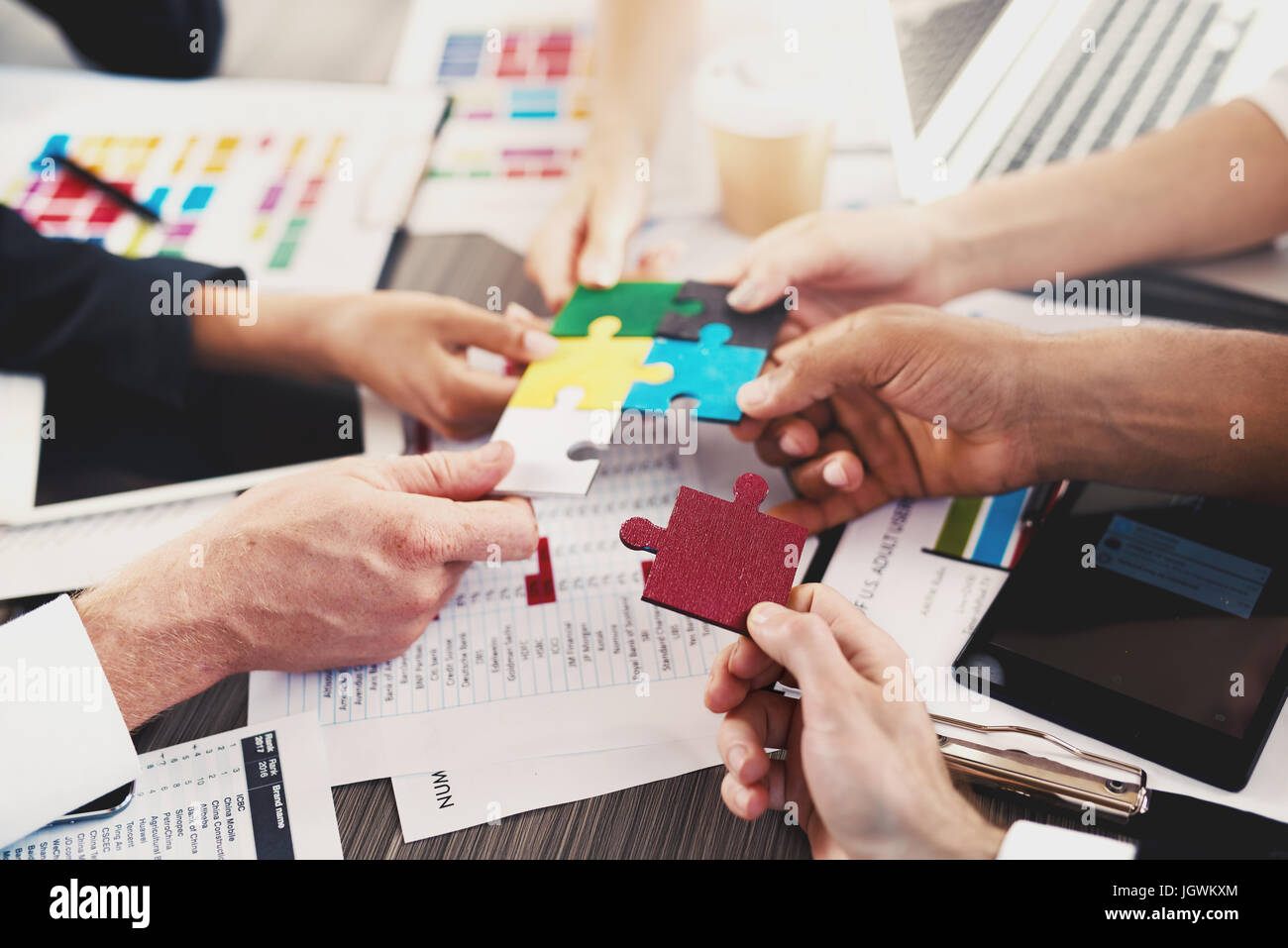 Team of businessmen work together to build a puzzle. Concept of unity and partnership - Stock Image