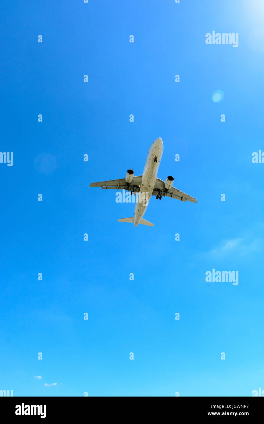 View from below of a flying airliner in landing approach or taking off. Stock Photo