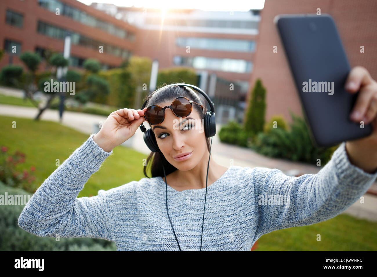 Young trendy caucasian woman taking selfie by tablet in city, wireless technology, posting to social media sites Stock Photo