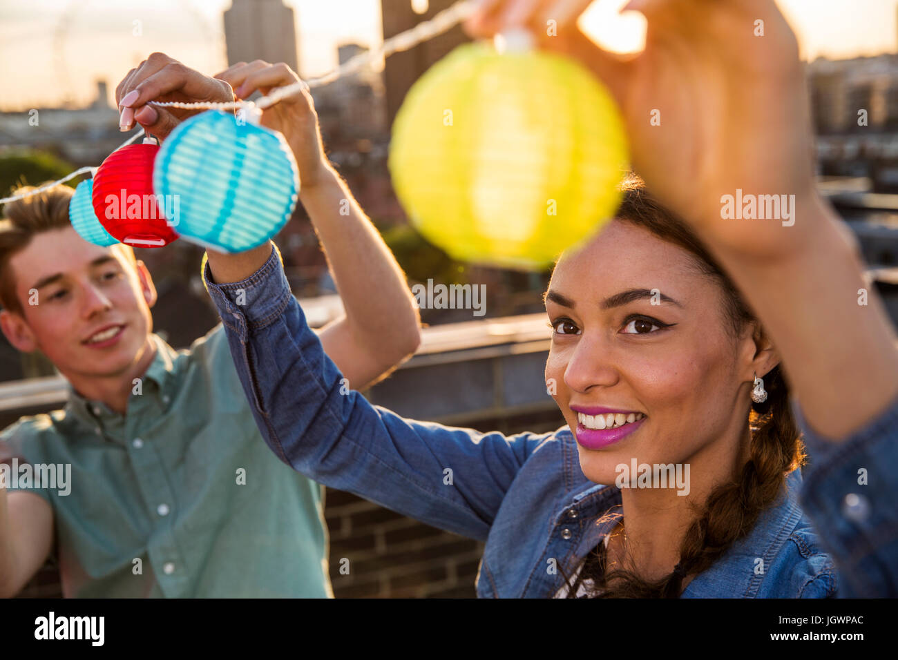 Young man and woman hanging lights at roof party in London, UK Stock Photo