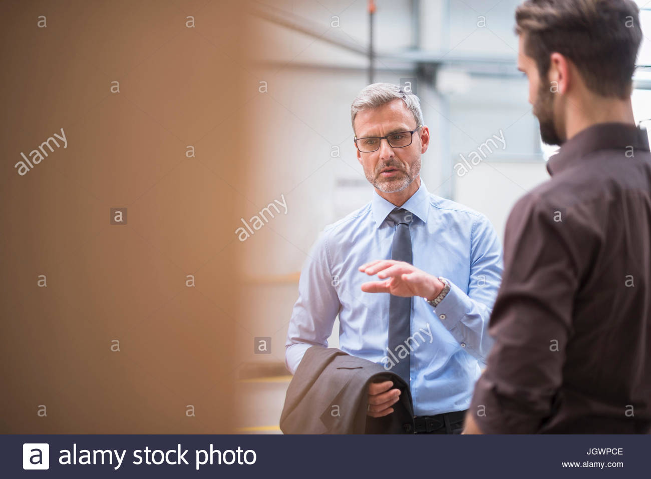Manager and supervisor having meeting in distribution warehouse - Stock Image