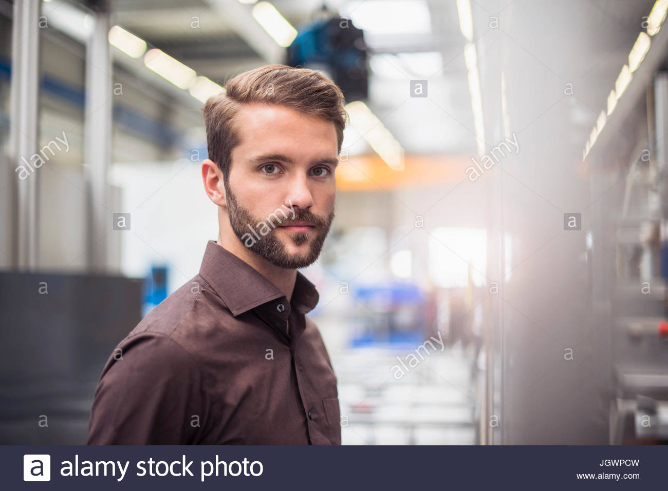 Portrait of young male supervisor in distribution warehouse - Stock Image