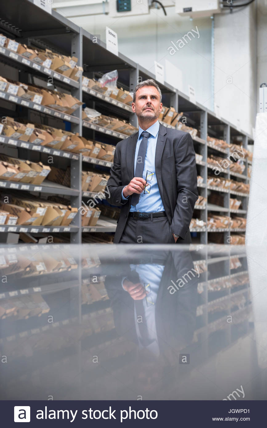 Business manager looking up in distribution warehouse - Stock Image