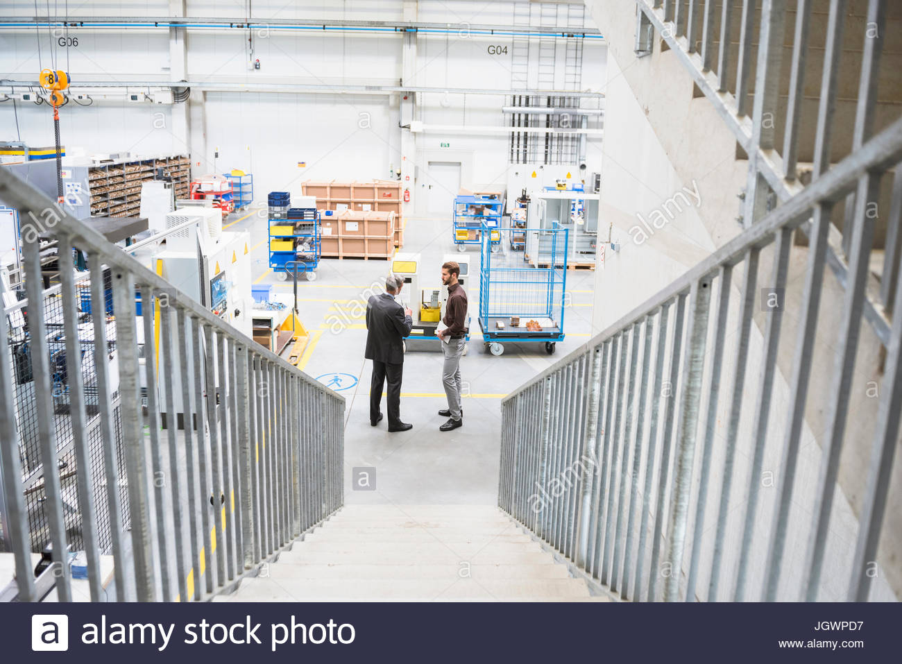 Supervisor and manager having discussion in distribution warehouse - Stock Image