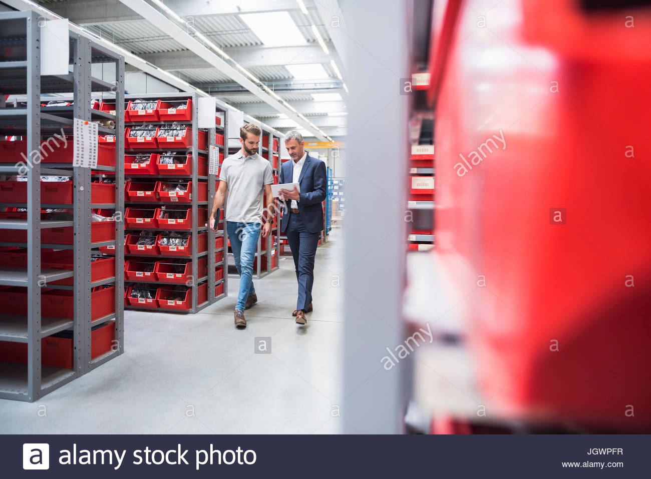 Manager and warehouse worker walking and talking in distribution warehouse - Stock Image