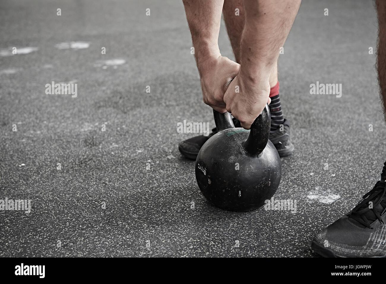 Man lifting kettlebell in cross training gym - Stock Image