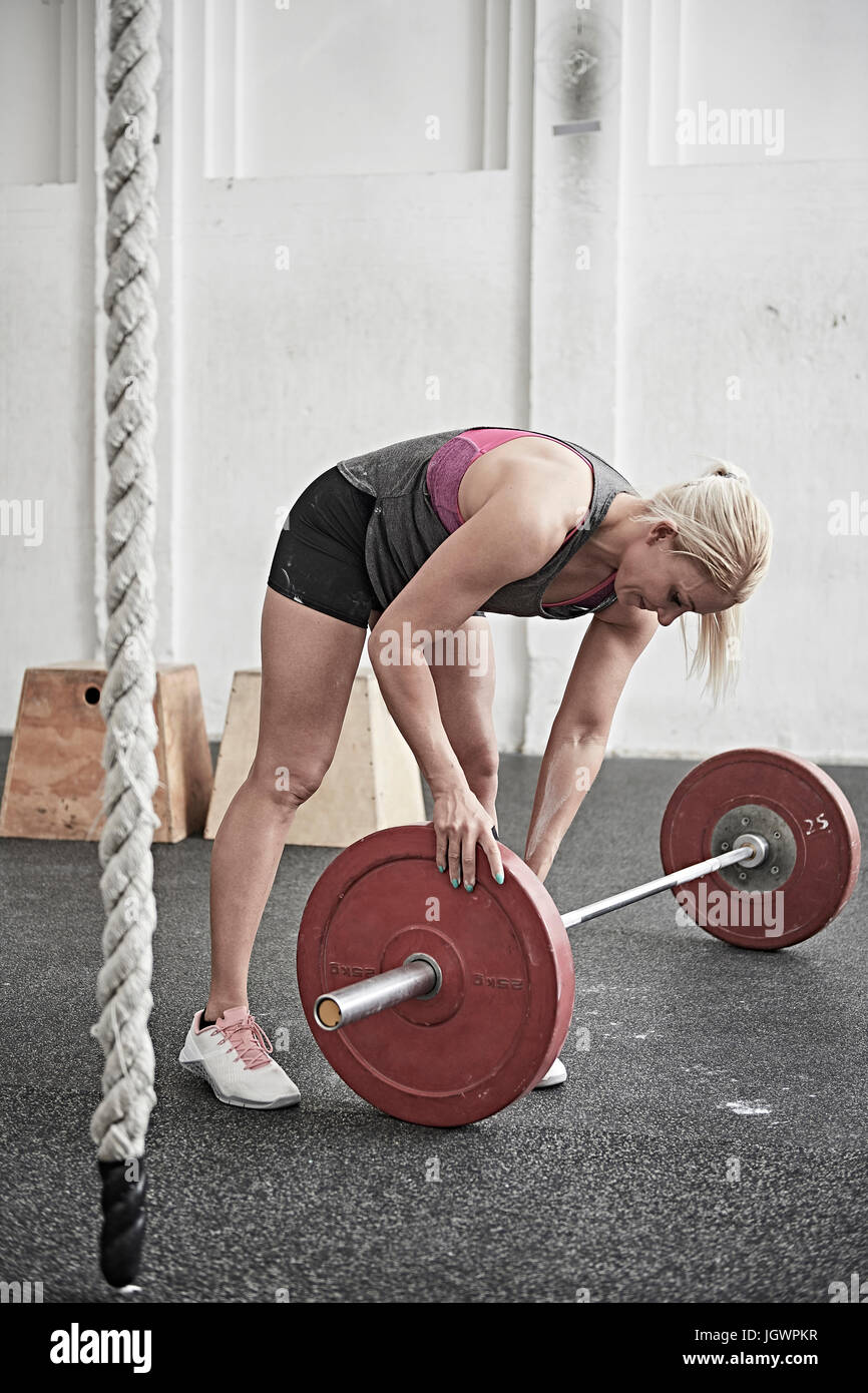 Woman adjusting barbell in cross training gym - Stock Image