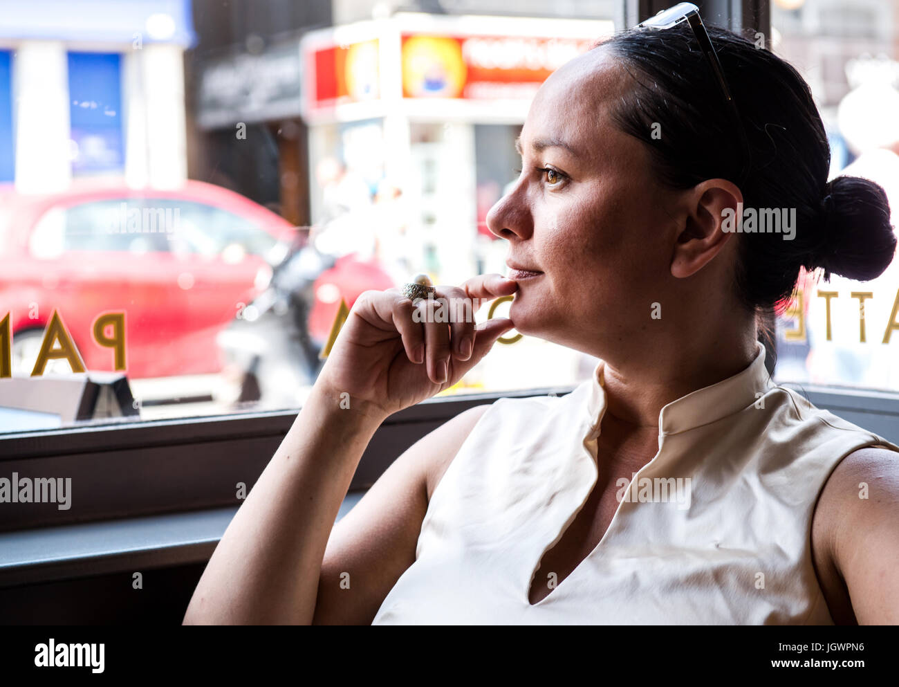 Businesswoman with hand on chin in coffee bar - Stock Image