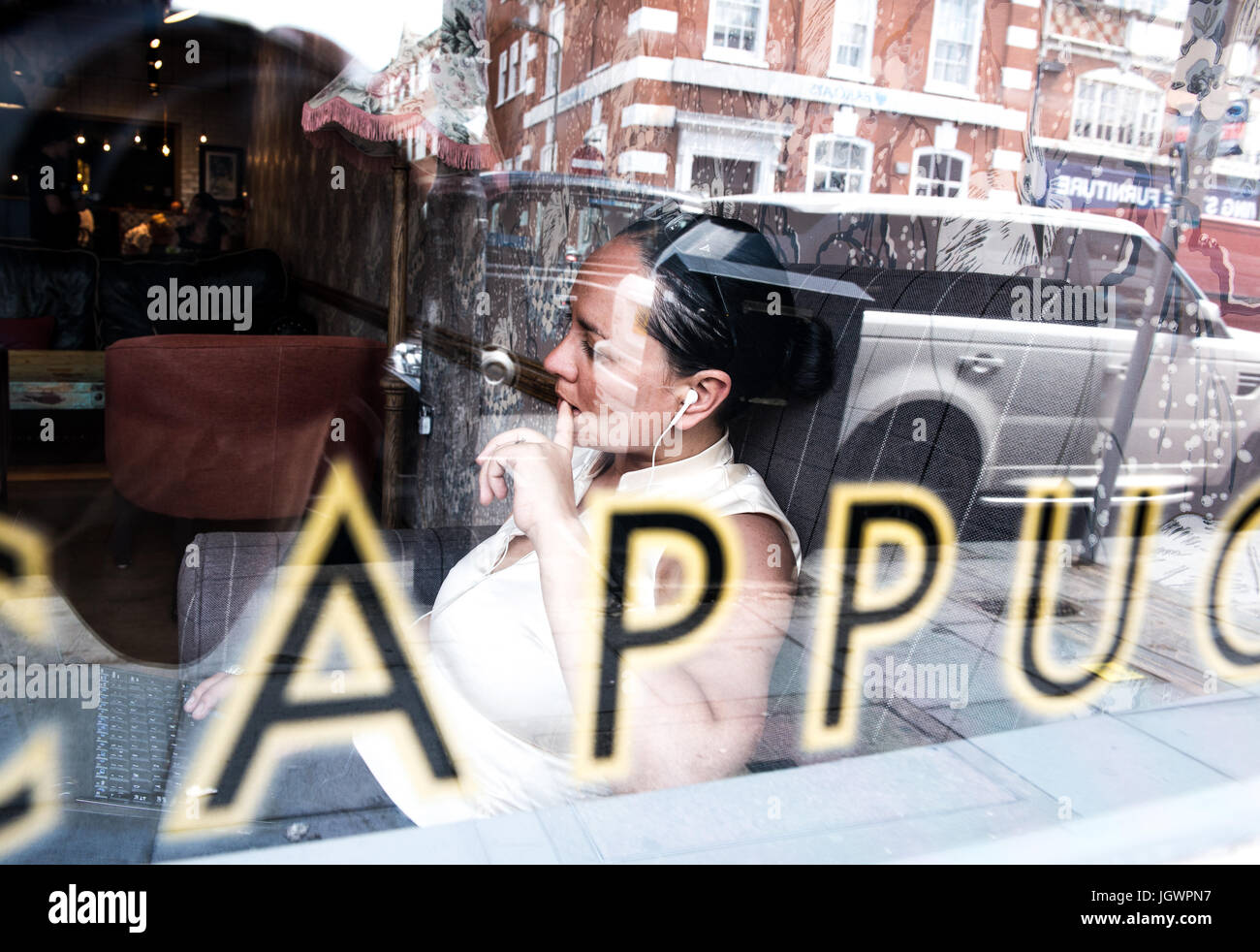 View through window of businesswoman working in coffee bar - Stock Image