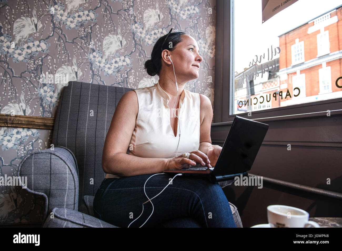 Businesswoman in coffee bar looking through window with laptop - Stock Image