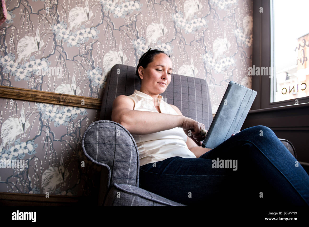 Businesswoman working on laptop in coffee bar - Stock Image