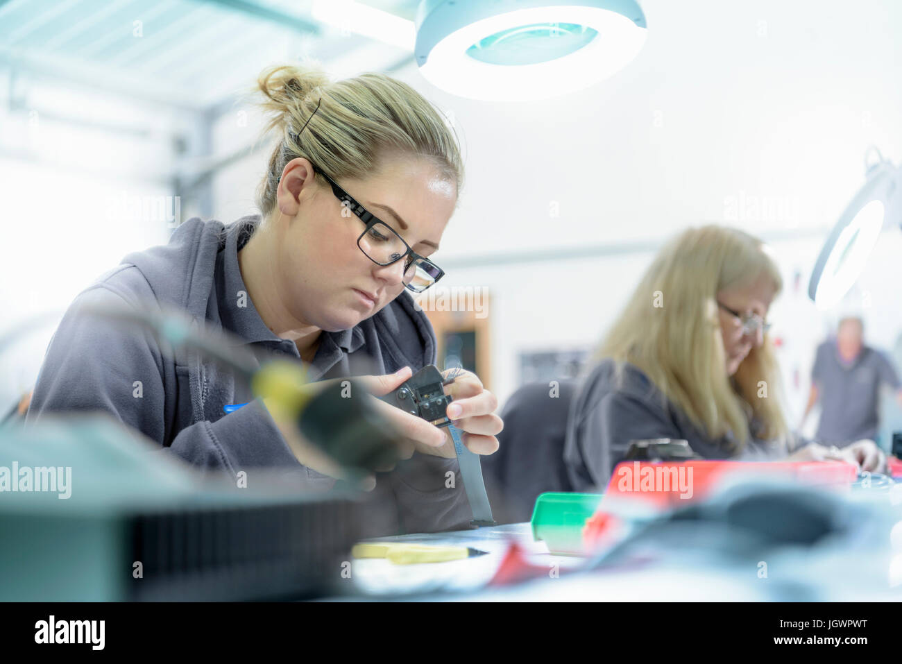 Female apprentice electrical engineers in cable finishing factory - Stock Image