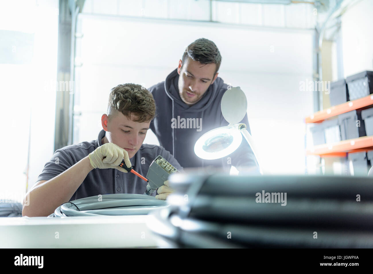 Apprentice and electrical engineer mentor in cable finishing factory - Stock Image