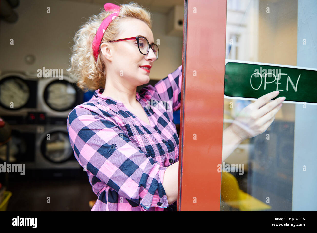 Female small business owner putting up open sign on laundrette doorStock Photo