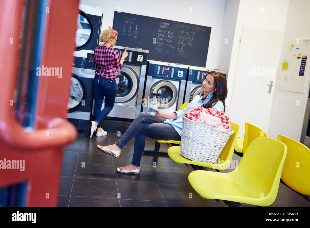 Bored woman waiting in laundrette - Stock Image
