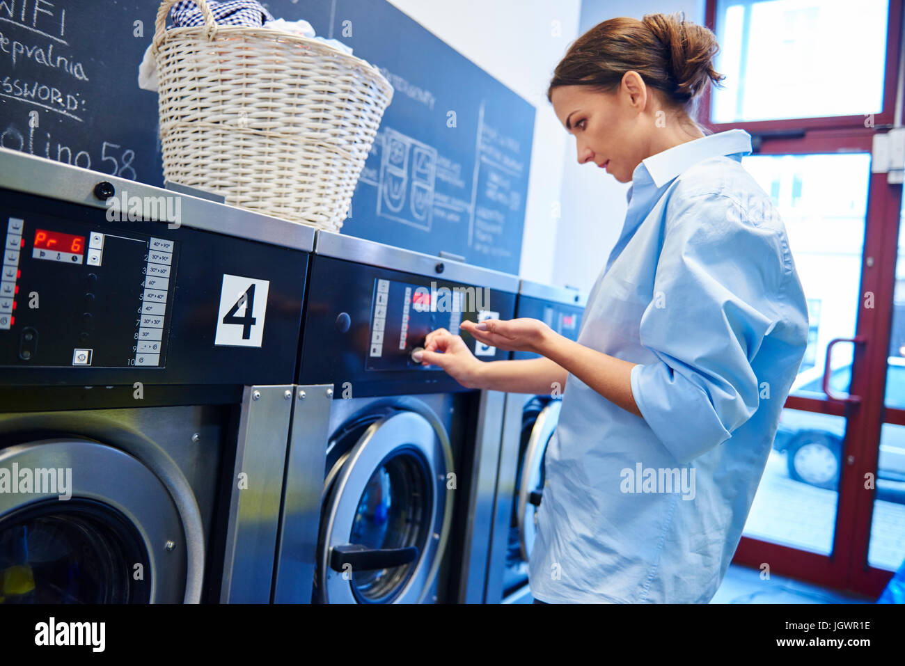 Woman inserting coins into washing machine at laundrette - Stock Image