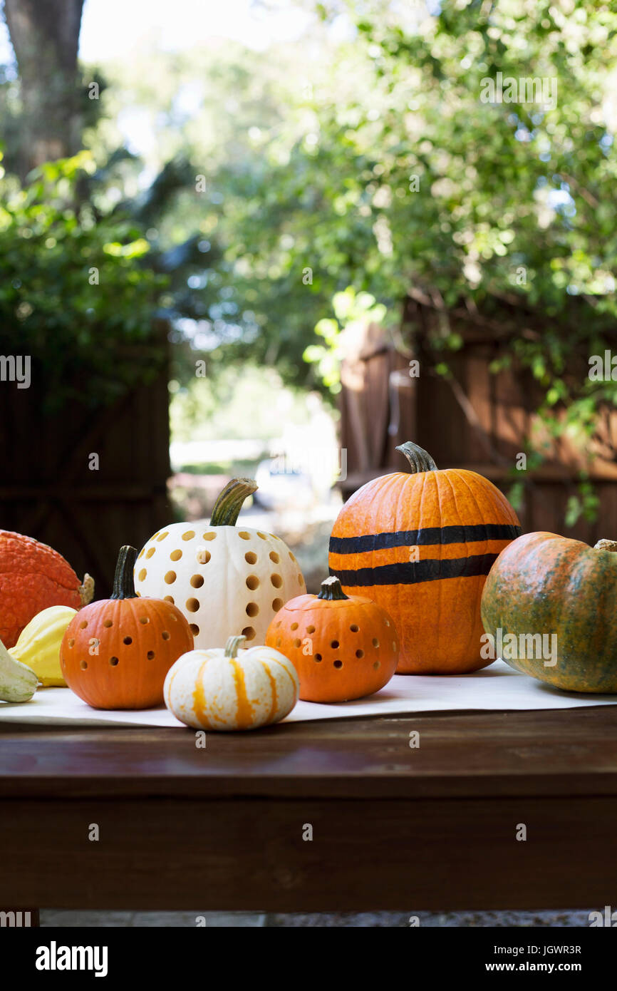 Striped and carved pumpkins on garden table - Stock Image