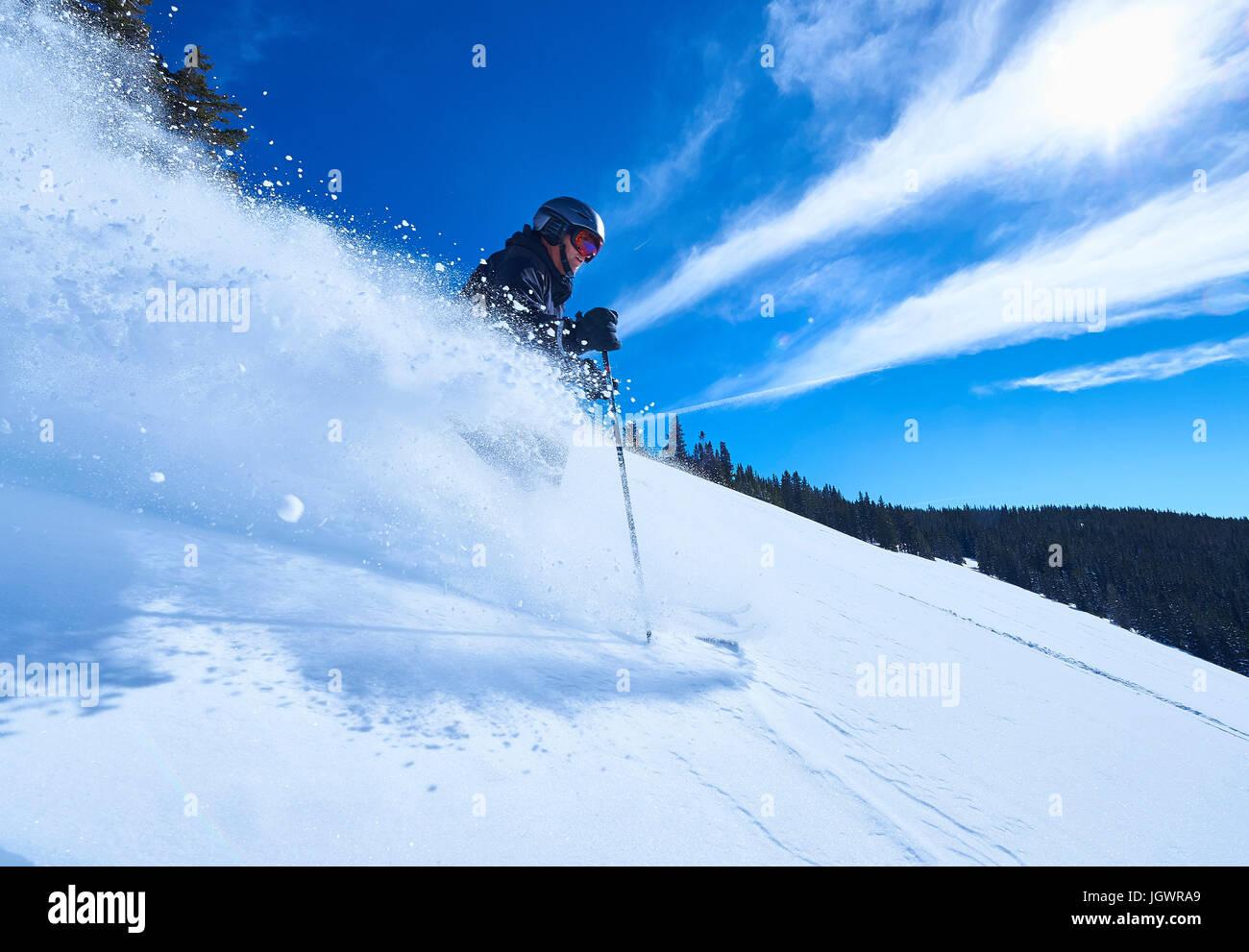 Man skiing down deep snow covered mountainside, Aspen, Colorado, USA - Stock Image