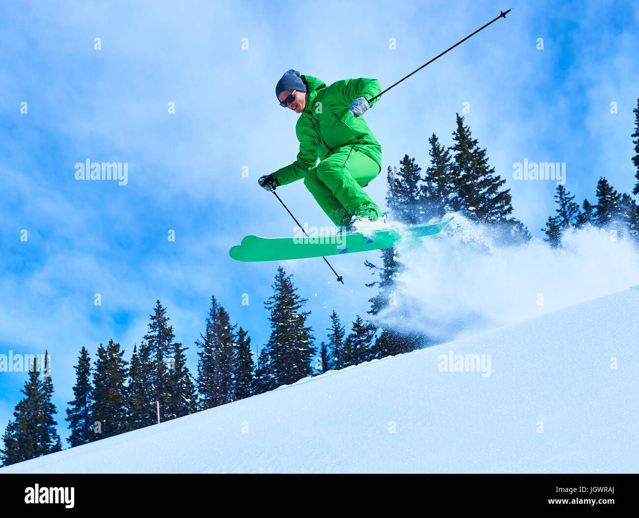 Man jumping while skiing down snow covered mountainside, Aspen, Colorado, USA - Stock Image