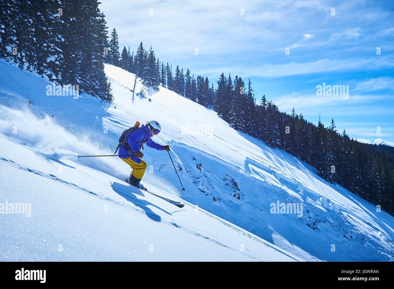 Man skiing down steep snow covered mountainside, Aspen, Colorado, USA - Stock Image