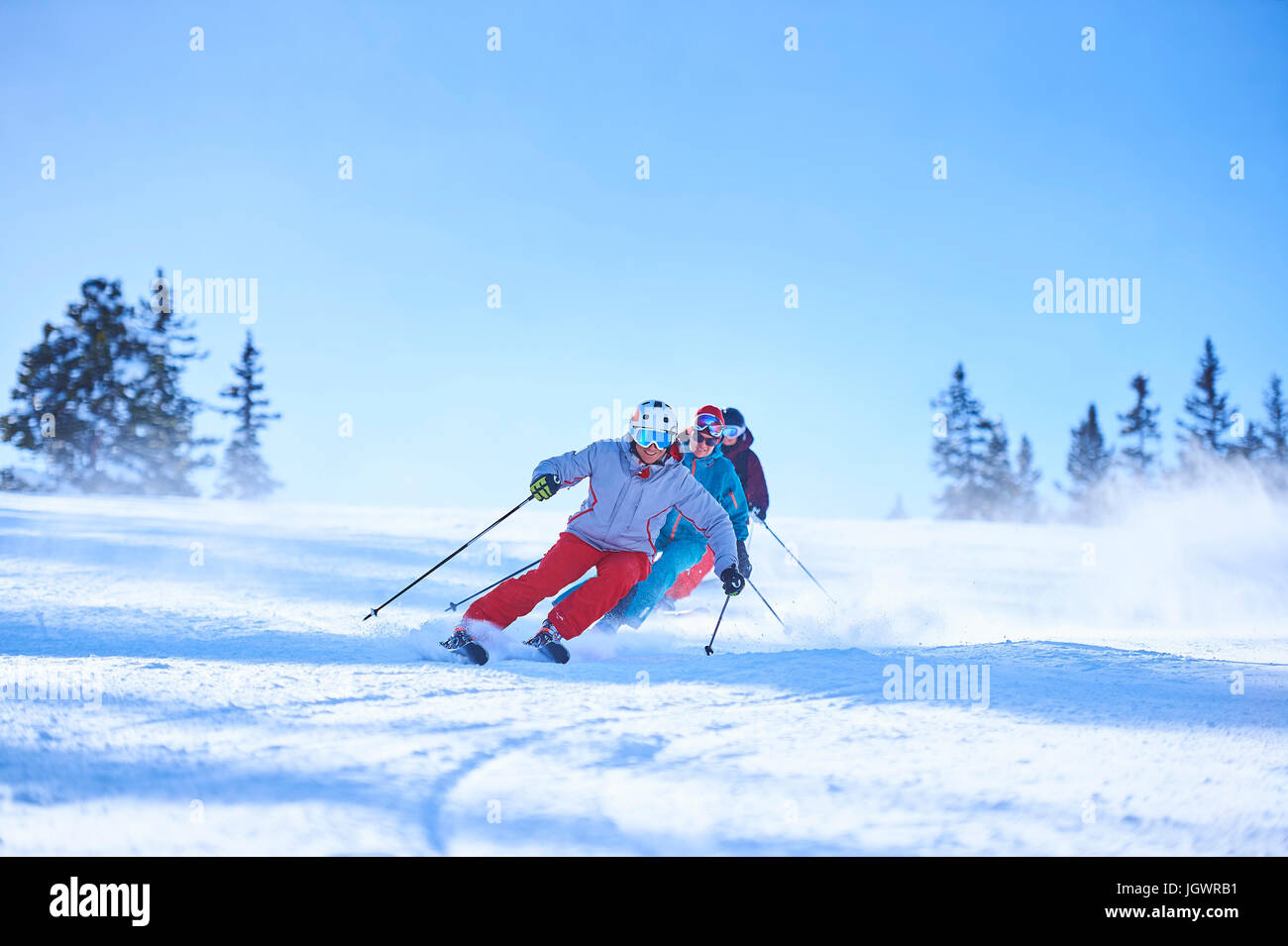Row of male and female skiers skiing down snow covered ski slope, Aspen, Colorado, USA - Stock Image