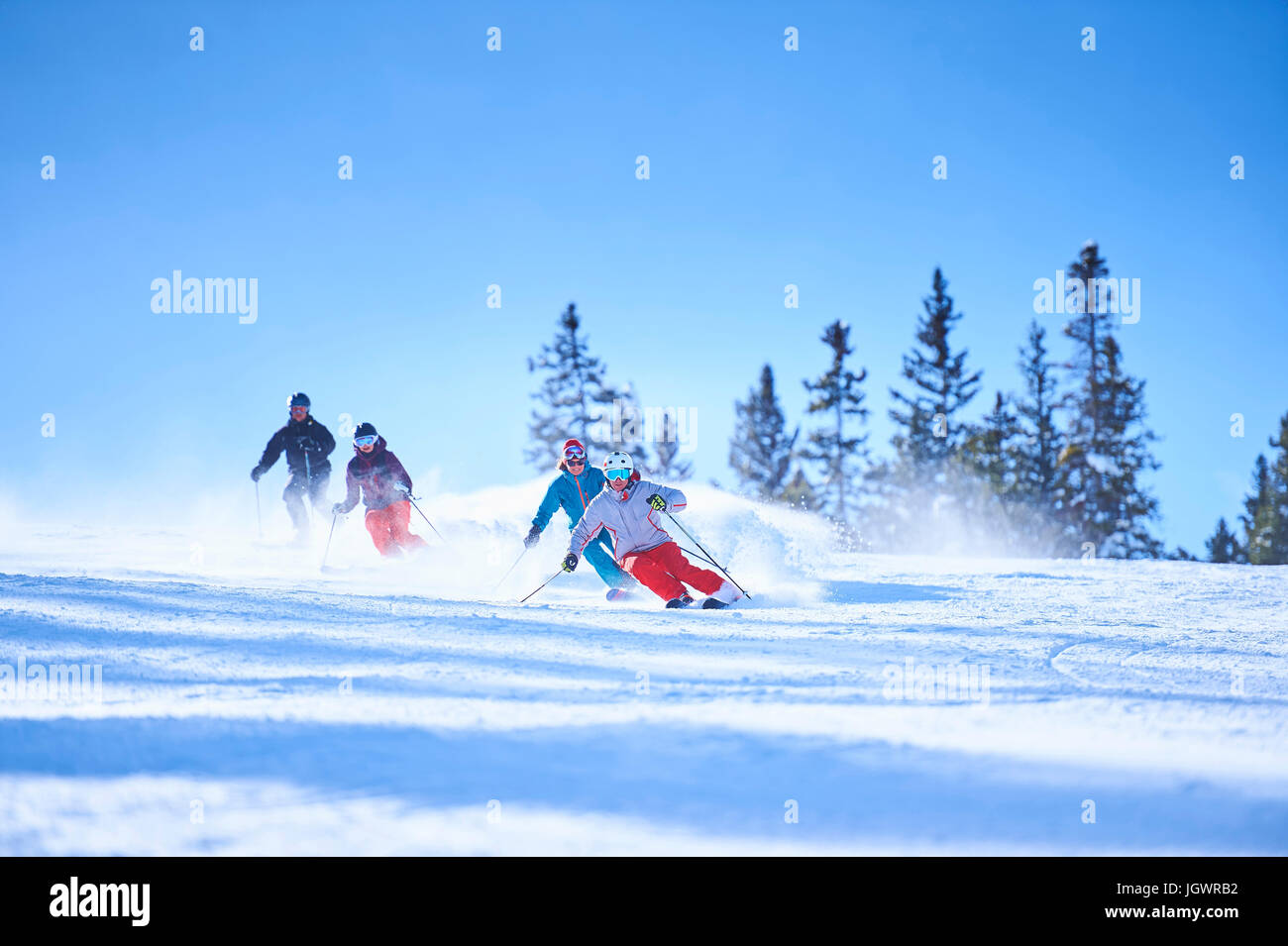 Male and female skiers skiing down snow covered ski slope, Aspen, Colorado, USA - Stock Image