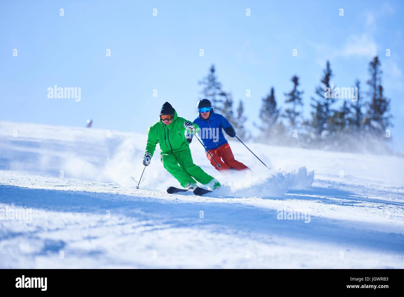 Two men skiing down snow covered ski slope, Aspen, Colorado, USA - Stock Image