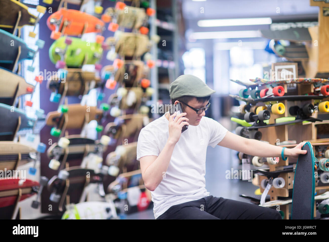 Young male skateboarder making smartphone call in skateboard shop - Stock Image