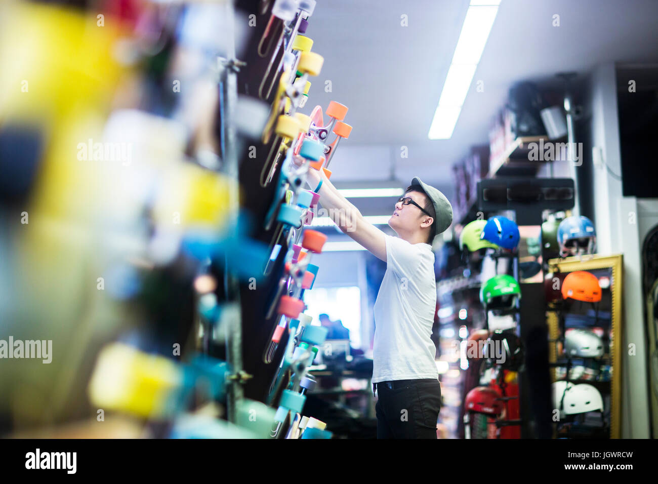 Young male skateboarder removing skateboard from wall in skateboard shop - Stock Image