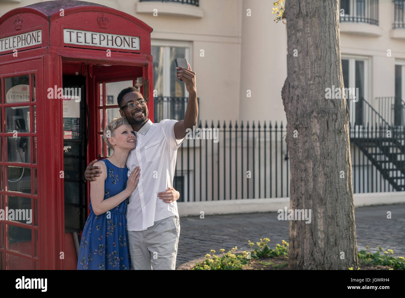 Young couple standing beside red telephone box, looking up, smiling - Stock Image